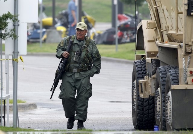 A SWAT officer walks through the parking lot of the Twin Peaks restaurant where nine members of a motorcycle gang were shot and killed in Waco, Texas May 19, 2015. Police warned of revenge attacks ...