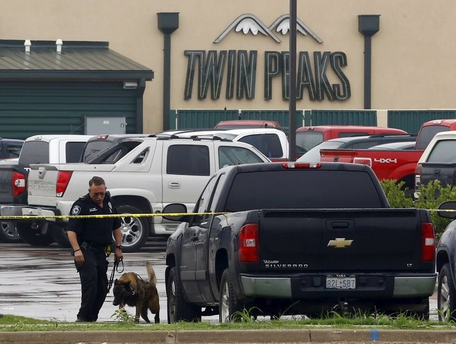 A police office and canine inspect vehicles in the parking lot of the Twin Peaks restaurant where nine members of a motorcycle gang were shot and killed in Waco, Texas May 19, 2015. Police warned  ...
