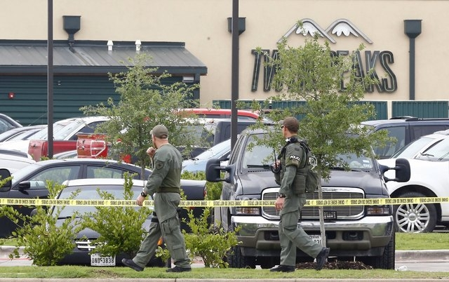 Police offices walk near a Twin Peaks restaurant where nine members of a motorcycle gang were shot and killed in Waco, Texas May 19, 2015. Police warned of revenge attacks from motorcycle gangs af ...