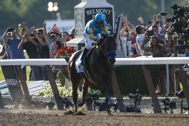 Fans cheer on as Jockey Victor Espinoza, aboard American Pharoah, passes the finish line to win the 147th running of the Belmont Stakes as well as the Triple Crown, in Elmont, New York June 6, 201 ...