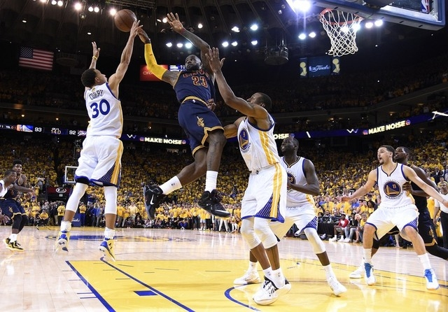 Jun 7, 2015; Oakland, CA, USA; Cleveland Cavaliers forward LeBron James (23) passes the ball against Golden State Warriors guard Stephen Curry (30) and Golden State Warriors guard Andre Iguodala ( ...