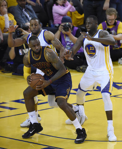 June 7, 2015; Oakland, CA, USA; Cleveland Cavaliers forward LeBron James (23) controls the ball against Golden State Warriors forward Draymond Green (23) and guard Andre Iguodala (9) during the ov ...