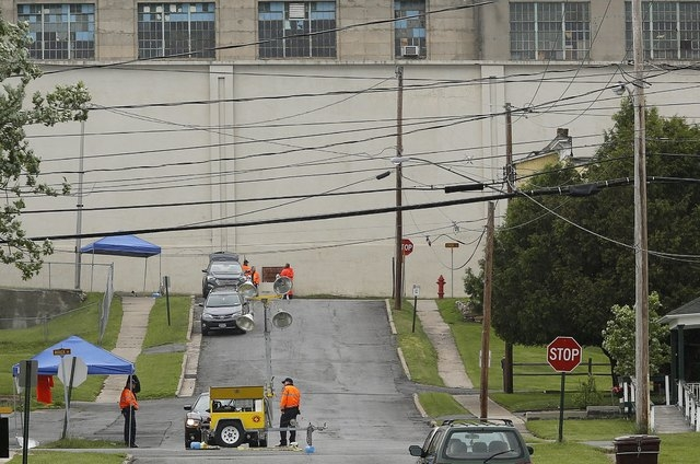 New York State Correctional Services officers (bottom) stand near a manhole where two convicted murderers emerged after escaping from the nearby Clinton Correctional Facility (in background) in Da ...