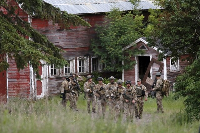 Police officers search a property near the Clinton Correctional Facility in Dannemora, New York, June 8, 2015. Authorities hunting for two convicted murderers who staged a brash prison break in up ...
