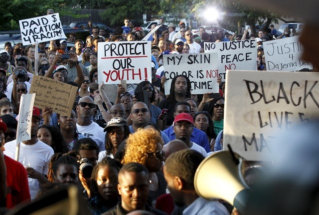 Protestors listen during a rally against what demonstrators call police brutality in McKinney, Texas June 8, 2015. Hundreds marched through the Dallas-area city of McKinney on Monday calling for t ...