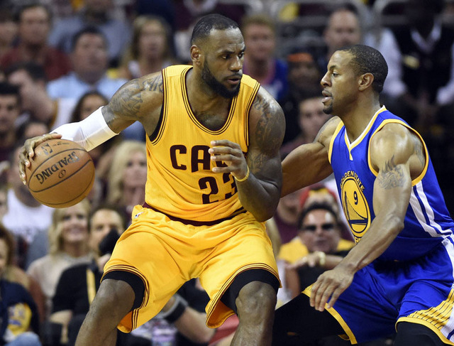 Jun 9, 2015; Cleveland, OH, USA; Cleveland Cavaliers forward LeBron James (23) handles the ball Golden State Warriors guard Andre Iguodala (9) during the second quarter in game three of the NBA Fi ...