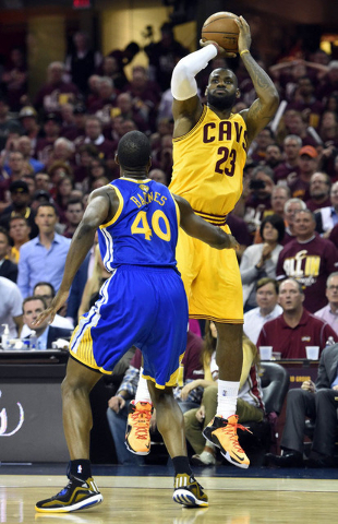 Jun 9, 2015; Cleveland, OH, USA; Cleveland Cavaliers forward LeBron James (23) shoots the ball over Golden State Warriors forward Harrison Barnes (40) during the third quarter in game three of the ...