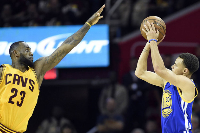 Jun 9, 2015; Cleveland, OH, USA; Golden State Warriors guard Stephen Curry (30) shoots the ball over Cleveland Cavaliers forward LeBron James (23) during the fourth quarter in game three of the NB ...