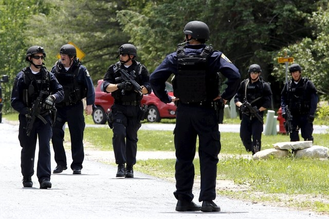 Law enforcement officials search a street near the Clinton Correctional Facility in Dannemora, New York, June 10, 2015. A daring weekend escape from a New York state maximum-security penitentiary, ...