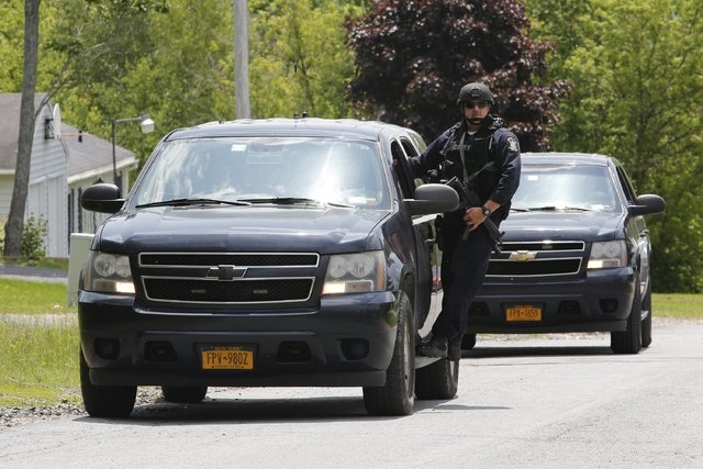 Law enforcement officials search a street near the Clinton Correctional Facility in Dannemora, New York, June 10, 2015.  As authorities searched for a fourth day for Richard Matt, 48, and his fell ...