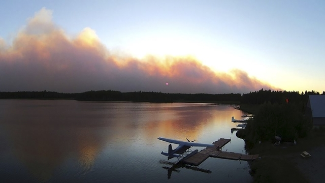 Smoke from an out of control wildfire partially blocks the sun over Willow Lake, near Willow, Alaska, in this picture courtesy of Mat-Su Borough taken June 14, 2015. (REUTERS/Mat-Su Borough/Stefan ...