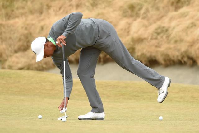 Jun 16, 2015; University Place, WA, USA; Tiger Woods picks up golf balls on the sixth green during practice rounds on Tuesday at Chambers Bay. Mandatory Credit: John David Mercer-USA TODAY Sports