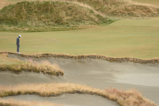 Jun 16, 2015; University Place, WA, USA; Tiger Woods looks into the sand on the seventh fairway during practice rounds on Tuesday at Chambers Bay. Mandatory Credit: John David Mercer-USA TODAY Sports