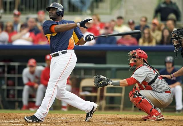 St. Louis Cardinals catcher Rob Johnson looks on as Houston Astros' Chris Carter hits a two-run homer off pitcher Jason Motte during the fifth inning of a MLB spring training game in Kissimmee, Fl ...