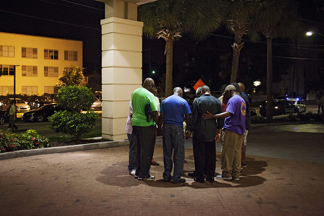 A small prayer circle forms nearby where police are responding to a shooting at the Emanuel AME Church in Charleston, South Carolina, June 17, 2015. A gunman opened fire on Wednesday evening at th ...