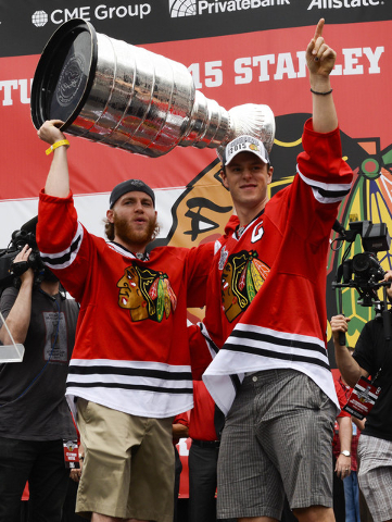 Jun 18, 2015; Chicago, IL, USA; Chicago Blackhawks center Jonathan Toews (19)   and right wing Patrick Kane (88) lift the Stanley Cup trophy at the rally during the 2015 Stanley Cup championship r ...