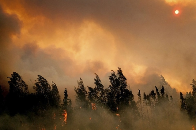 The setting sun is partially obscured by smoke from an out of control wildfire on the Parks Highway near Willow, Alaska, in this picture courtesy of Mat-Su Borough taken June 14, 2015. (REUTERS/Ma ...