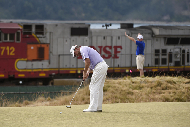 Jun 18, 2015; University Place, WA, USA; Lee Westwood putts on the 17th green as a train passes by in the background in the first round of the 2015 U.S. Open golf tournament at Chambers Bay. (Kyle ...