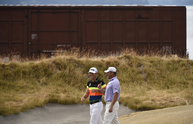 Jun 18, 2015; University Place, WA, USA; Lee Westwood (right) and Billy Horschel (left) laugh as a train passes by them on the 17th green in the first round of the 2015 U.S. Open golf tournament a ...