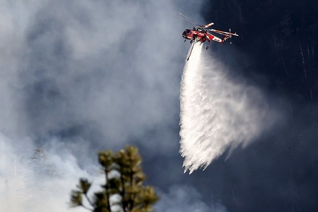 A helicopter makes a water drop on a wildfire near Jenks Lake in the San Bernardino National Forest, California, United States, June 18, 2015. Wildfires raging in three West Coast states have forc ...