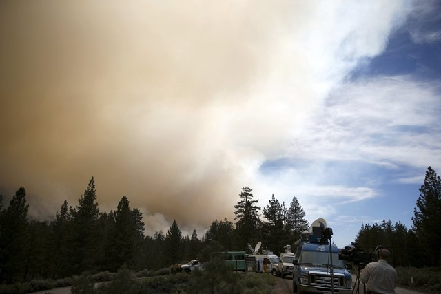 News crews watch a wildfire spread in Heart Bar in the San Bernardino National Forest near Big Bear Lake, California, United States, June 18, 2015. Wildfires raging in three West Coast states have ...