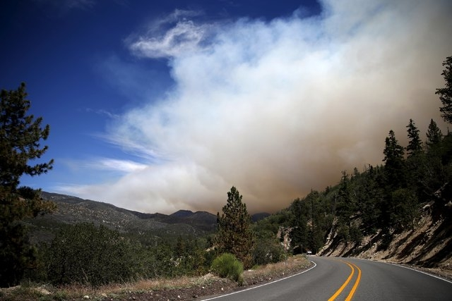 A wildfire spreads in Heart Bar in the San Bernardino National Forest near Big Bear Lake, California, United States, June 18, 2015. Wildfires raging in three West Coast states have forced more tha ...