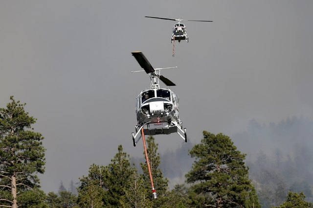 Helicopters pick up water to drop on a wildfire at Jenks Lake in the San Bernardino National Forest, California, United States, June 18, 2015. Wildfires raging in three West Coast states have forc ...
