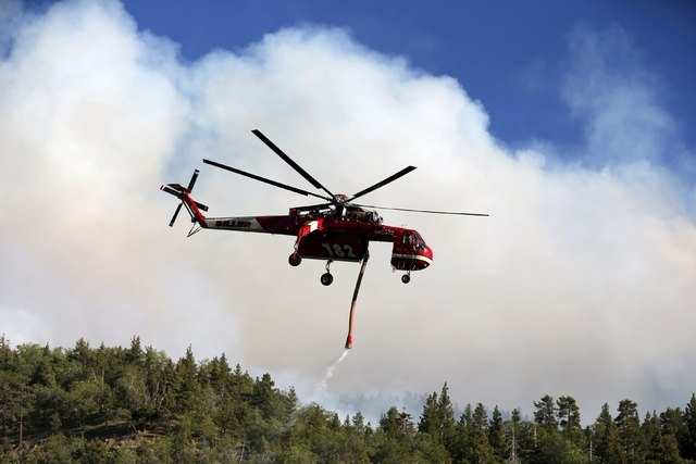 A helicopter picks up water to drop on a wildfire at Jenks Lake in the San Bernardino National Forest, California, United States, June 18, 2015. Wildfires raging in three West Coast states have fo ...