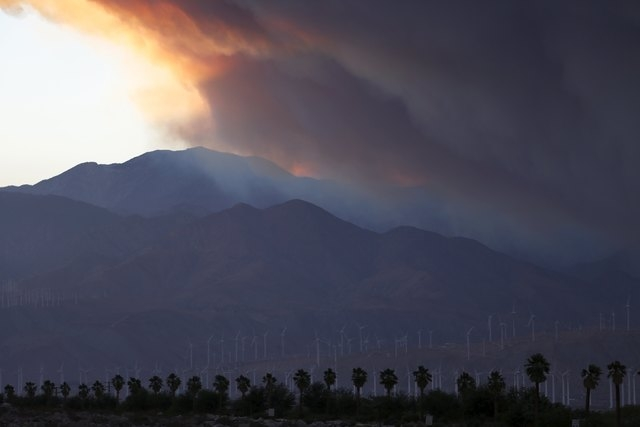 A smoke plume from the Lake Fire in the San Bernardino National Forest is seen at sunset, rising over the Coachella Valley from Palm Springs, California, United States June 18, 2015.  Some 500 fir ...