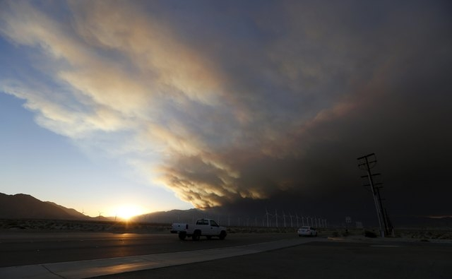 A smoke plume from the Lake Fire in the San Bernardino National Forest is seen at sunset, rising over a windmill farm from Palm Springs, California June 18, 2015.  Some 500 firefighters backed by  ...