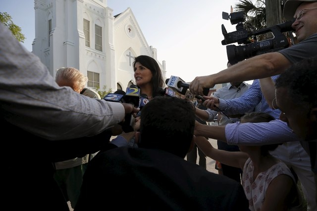 South Carolina Gov. Nikki Haley, center, talks to reporters outside the Emanuel African Methodist Episcopal Church in Charleston, South Carolina, June 19, 2015, two days after a mass shooting left ...