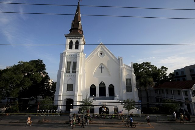 Members of the public continue to pay their respects and leave flowers outside the Emanuel African Methodist Episcopal Church in Charleston, South Carolina June 19, 2015, two days after a mass sho ...