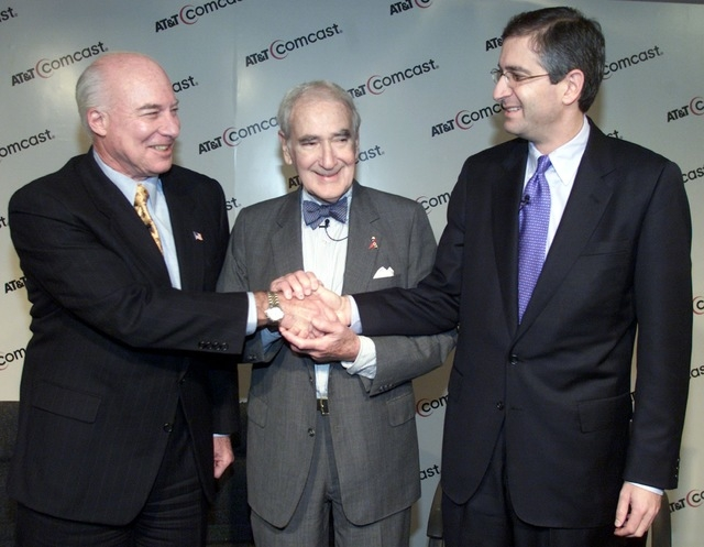 AT&T Chairman and CEO Michael Armstrong, left, shakes hands with Comcast Chairman Ralph Roberts and his son, Comcast President Brian Roberts before a press conference to announce the merger of AT& ...
