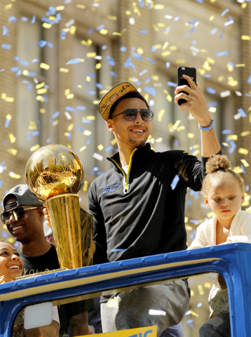 Jun 19, 2015; Oakland, CA, USA; Golden State Warriors guard Stephen Curry takes a photo with his cellular phone during the Golden State Warriors 2015 championship celebration in downtown Oakland.  ...