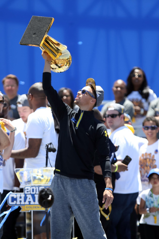 Jun 19, 2015; Oakland, CA, USA; Golden State Warriors guard Stephen Curry (30) holds up the trophy during the Golden State Warriors 2015 championship celebration at the Henry J. Kaiser Convention  ...