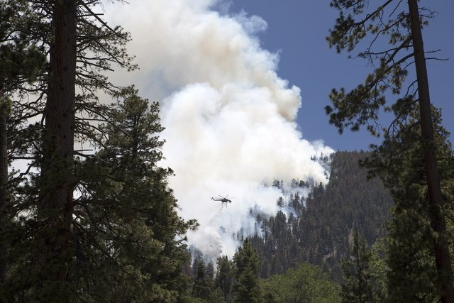 A firefighting helicopter drops water near Camp Bravo summer camp as firefighters battle the Lake Fire in the San Bernardino National Forest, California June 19, 2015.  Wildfires raging in three W ...
