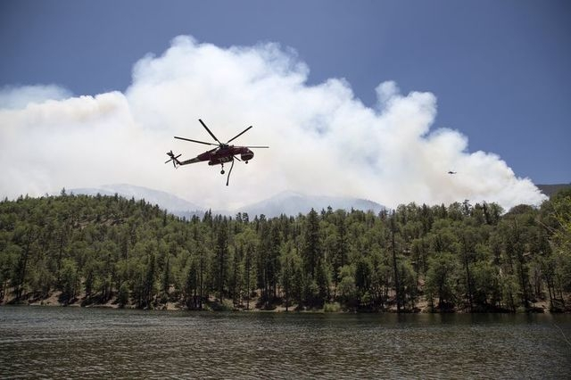 Firefighting helicopters fill up with water from Jenks Lake as firefighters battle the Lake Fire in the San Bernardino National Forest, California June 19, 2015. (REUTERS/David McNew)