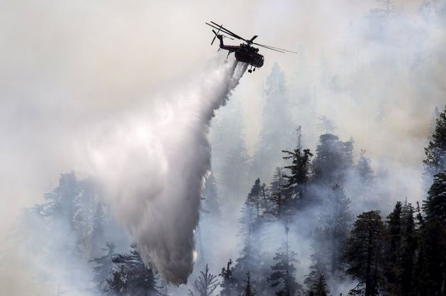 A firefighting helicopter drops water near Camp Bravo summer camp as firefighters battle the Lake Fire in the San Bernardino National Forest, California June 19, 2015. (REUTERS/David McNew)