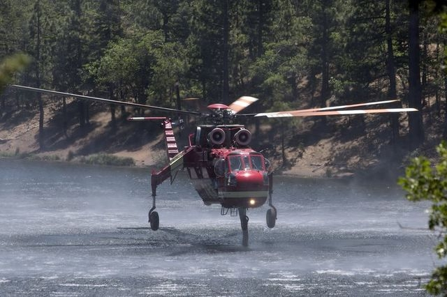 A firefighting helicopter fills up with water from Jenks Lake as firefighters battle the Lake Fire in the San Bernardino National Forest, California June 19, 2015. (REUTERS/David McNew)