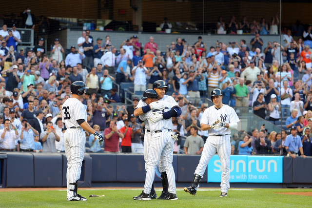 Jun 19, 2015; Bronx, NY, USA; New York Yankees designated hitter Alex Rodriguez (13) is greeted at home after hitting a solo home run against the Detroit Tigers by New York Yankees right fielder C ...