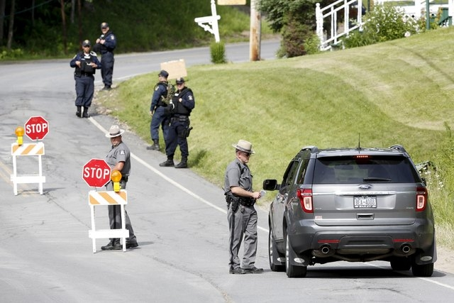 A law enforcement officer checks a vehicle at a roadblock along County Route 41 during a search for an escaped prisoner south of Malone, New York, June 27, 2015. Law enforcement officers on Friday ...