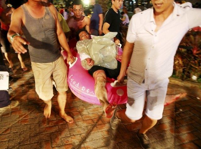 People carry an injured victim from an accidental explosion during a music concert at the Formosa Water Park in New Taipei City, Taiwan, June 27, 2015. (Chen Bo/Reuters)