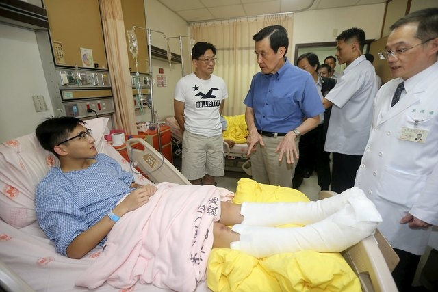 Taiwan President Ma Ying-jeou (C in blue) visits a man who sustained injuries in a fire at the Formosa Fun Coast water park at Taipei Veterans General Hospital in Taipei, Taiwan, June 28, 2015. Th ...