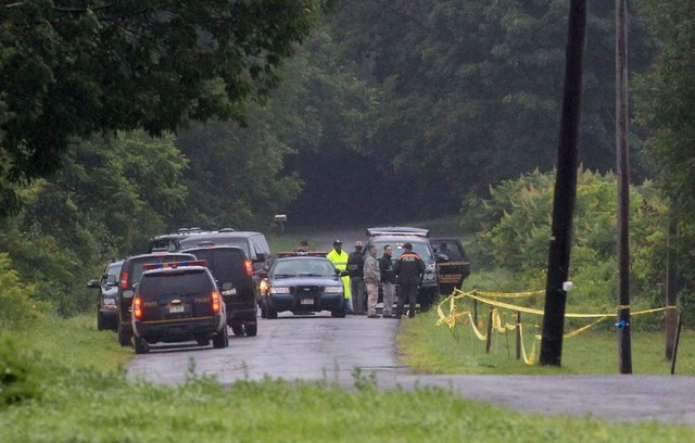 State troopers and investigators tape off Coveytown Road, where escaped prisoner David Sweat was captured, in Constable, New York, June 28, 2015. (Reuters/Christinne Muschi)