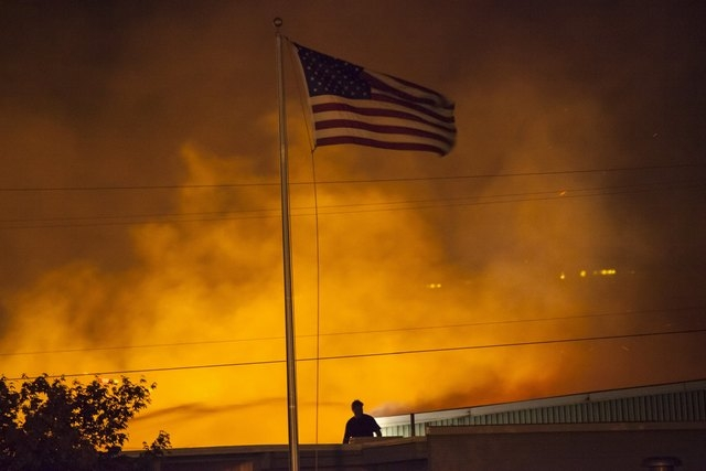 A U.S. flag is seen as a commercial building burns after being ignited by the Sleepy Hollow fire in Wenatchee, Washington June 29, 2015.  Emergency officials ordered hundreds of people to leave th ...
