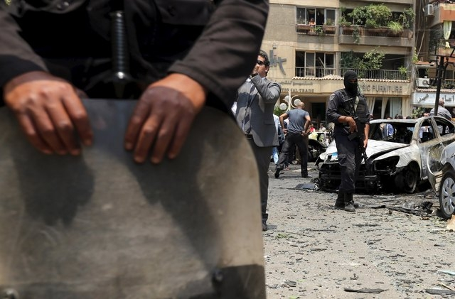 A policeman secures the site of a car bomb attack on the convoy of Egyptian public prosecutor Hisham Barakat near his house at Heliopolis district in Cairo, Egypt June 29, 2015. Barakat died from  ...