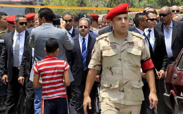 Egyptian Interior Minister Magdy Abdel Ghaffar (C) investigates the site of a car bomb attack on the convoy of Egyptian public prosecutor Hisham Barakat near his house at Heliopolis district in Ca ...