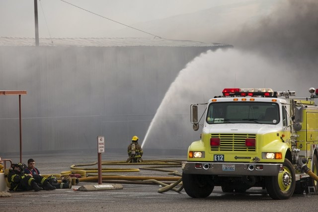 Firefighters rest as their colleague continues to battle flames that burned through the night at a commercial building that was ignited by the Sleepy Hollow fire in Wenatchee, Washington June 29,  ...
