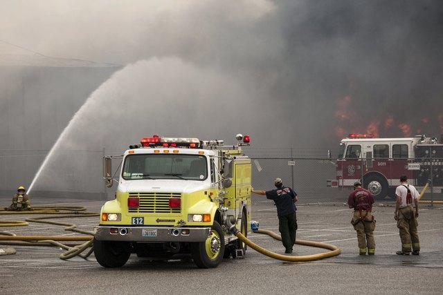 Firefighters rest as their colleague continues to battle flames that has burned through the night at a commercial building that was ignited by the Sleepy Hollow fire in Wenatchee, Washington June  ...