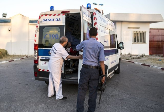 A police officer checks an ambulance carrying British tourists, who were wounded during the Imperial Marhaba hotel attack by a gunman, as they arrive to board the Royal Air Force (RAF) jet at Mona ...